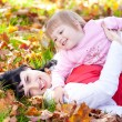 Beautiful young mother and her daughter lying on the autumn leav — Stock Photo #19770723
