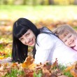 Beautiful young mother and her daughter lying on the autumn leav — Stock Photo #19770843