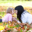 Beautiful young mother and her daughter lying on the autumn leav — Stock Photo #19771257