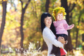 Beautiful young mother holding her daughter in a wreath of maple — 图库照片