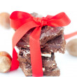 Background of stack of chocolate with red ribbon and nuts — Stock Photo