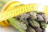 Asparagus tied with measuring tape isolated on white — Stock Photo
