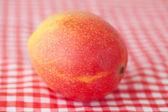 Mango fruit on checkered fabric — Stockfoto