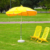 Yellow umbrellas and loungers standing on the grass — Stock Photo