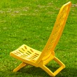 Yellow lounger standing on the grass — Stock Photo