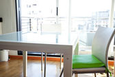 Table and chairs in front of windows in the room — Stock Photo
