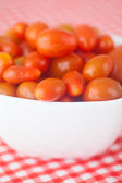 Cherry tomatos in bowl on checkered fabric — Stock Photo