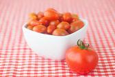 Pomodori ciliegia e pomodori nella ciotola sul tessuto a scacchi — Foto Stock