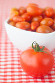 Cherry tomatos and tomatos in bowl on checkered fabric — Stock Photo