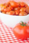 Cherry tomatos and tomatos in bowl on checkered fabric — Stock Photo