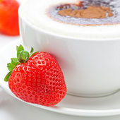 Cappuccino in a cup in the shape of hearts and strawberries isol — Stock Photo