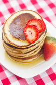 Pancakes, honey and strawberry on checkered fabric — 图库照片