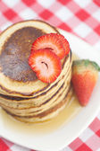 Pancakes, honey and strawberry on checkered fabric — Stock Photo