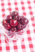 Cherries in a glass bowl on checkered fabric — Stock Photo