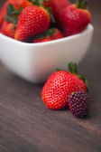 Red juicy strawberry  in a bowl and blackberry on a wooden surfa — Stock Photo