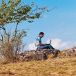 Young man using laptop sitting on a hill against the blue sky — Stock Photo #7312656