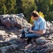 Young man using laptop sitting on a rock slope — Stock Photo #7312820
