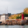 Small red lighthouse and old house — Stock Photo