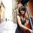 Stock Photo: Womplaying double bass on street
