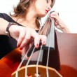 Woman in black dress play double bass. Low point view - Stock Photo