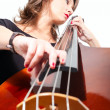 Stock Photo: Womin black dress play double bass. Low point view