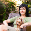 Beautiful woman in chair with little dog in garden — Stock Photo