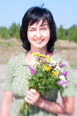 Sunny outdoors vintage portrait of woman with bunch of field flo — Stock Photo