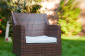 Empty chair with pillow outdoors in sunny summer garden — Stock Photo