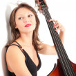 Stock Photo: Womin black dress play double bass by white wall