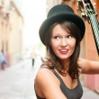 Stock Photo: Womin hat playing double bass on street