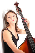 Woman in black dress play double bass by white wall — Stock Photo