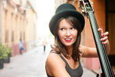 Woman in hat playing double bass on the street — Stock Photo