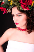 Beautiful woman in flower wreath portrait, white dress and red s — Stock Photo