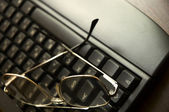 Black keyboard and glasses — Stock Photo