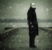 Man with white mask near the river — Stock Photo