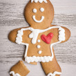 Gingerbread man with red heart and broken leg — Stock Photo