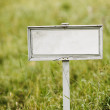 Stock Photo: Empty signboard on green field