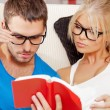 Couple at home with book - Foto Stock