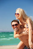 Happy couple in sunglasses on the beach — Stockfoto