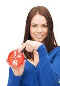 Woman holding alarm clock — Stockfoto