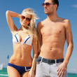 Happy couple in sunglasses on the beach — Stock Photo #12592221