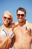 Lyckliga par solglasögon på stranden — Stockfoto