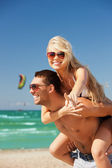 Happy couple in sunglasses on the beach — Photo