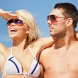 Happy couple in sunglasses on the beach — Stock Photo #12619979