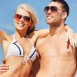 Happy couple in sunglasses on the beach — Stock Photo #12664796