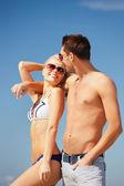 Couple heureux en lunettes de soleil sur la plage — Photo