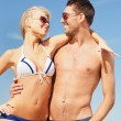 Happy couple in sunglasses on the beach — Stock Photo #12885666