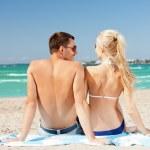 Happy couple sitting on the beach — Stock Photo
