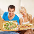 Romantic couple eating pizza at home — Stok fotoğraf