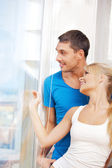 Happy couple at the window — Stock Photo